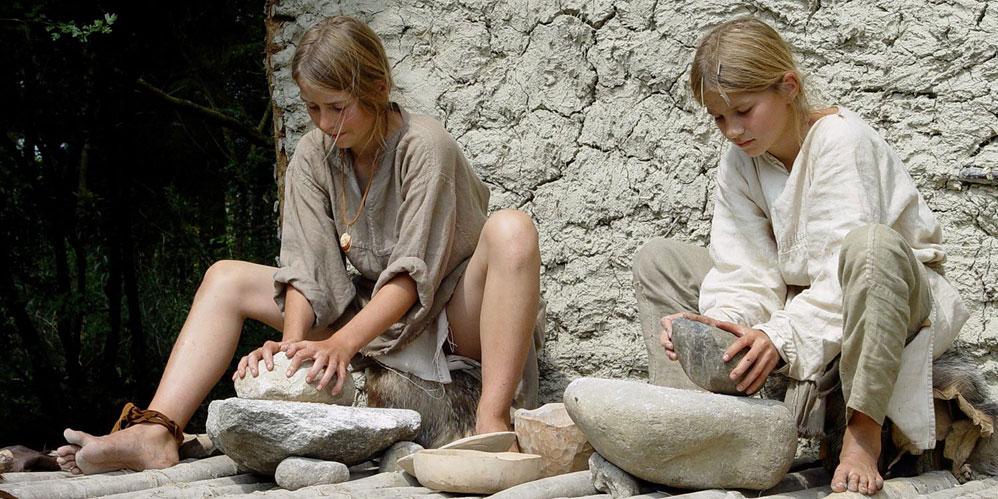 Mahlen der Getreidekörner auf steinernen Handmühlen. «Pfahlbauer von Pfyn» im Sommer 2007. Foto SRF, Schweiz aktuell, Patrick Gautschy.